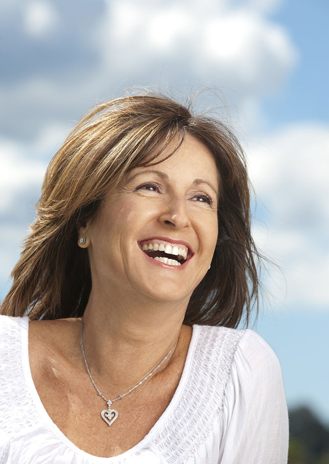 Happy mature woman with wind in her hair and blue sky background